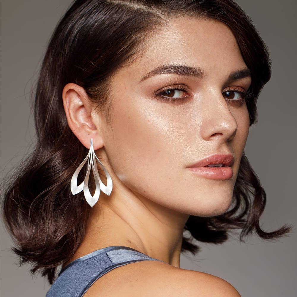 Triple dancing flame earrings on model side view