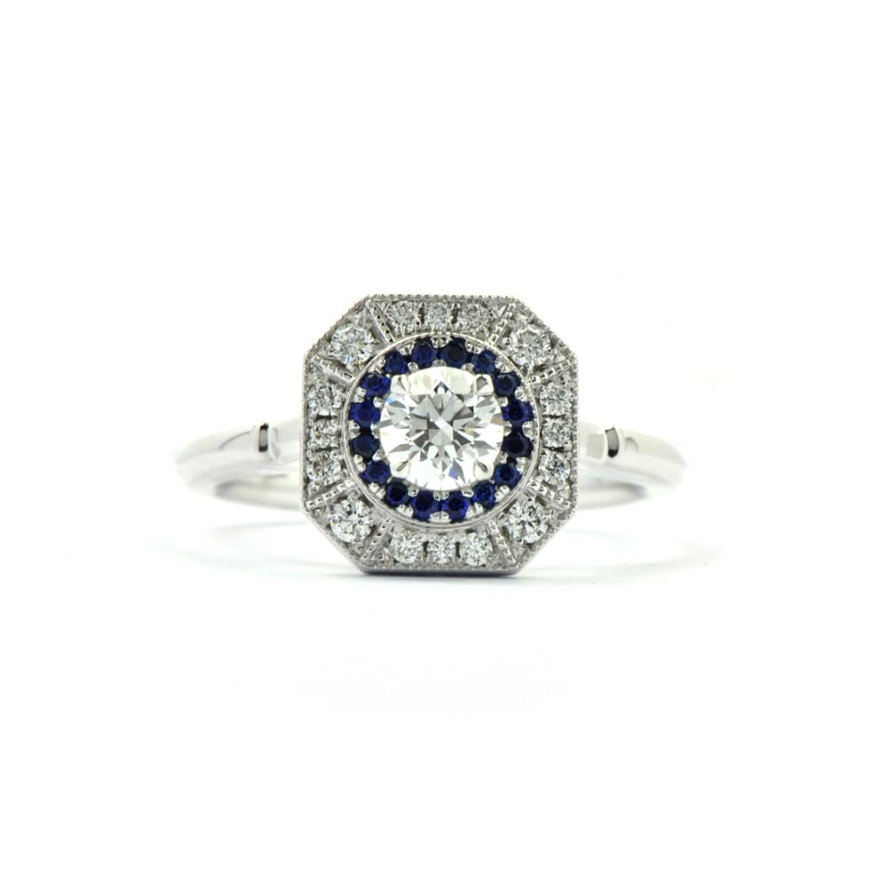 Art Deco style ring in white gold with round centre diamond, halo of sapphires and surrounded by a halo of diamonds