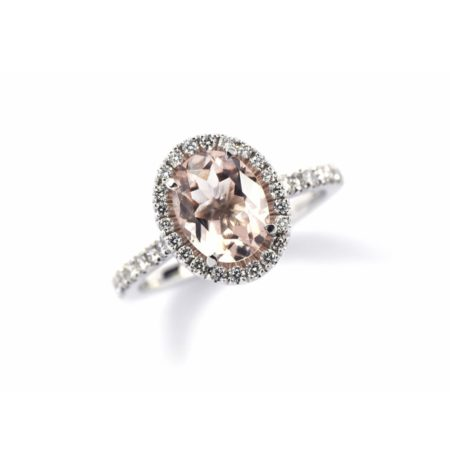 White gold ring with pale pink oval morganite centre stone, diamond halo surround and diamonds set into the band.