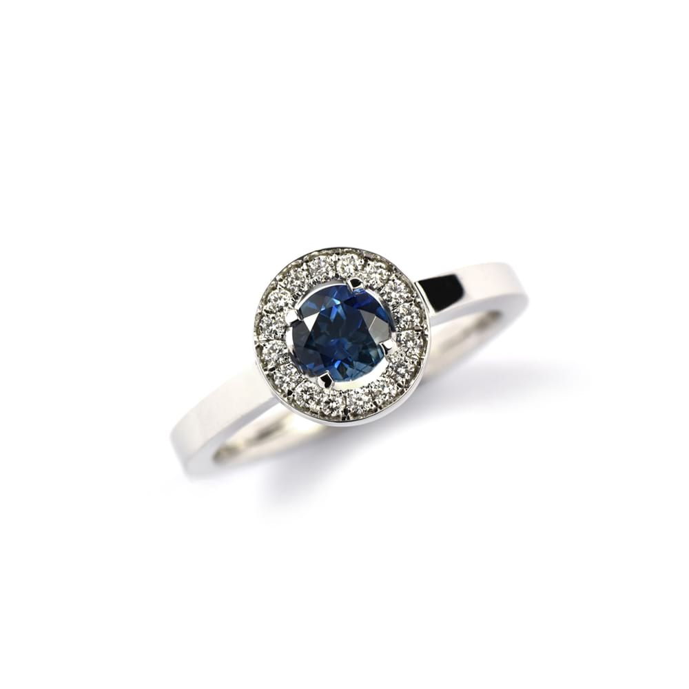 WHITE GOLD RING WITH ROUND BLUE SAPPHIRE SET WITH A DIAMOND SURROUND IN A ROUND SETTING