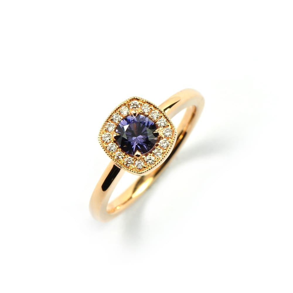 ROSE GOLD RING WITH BLUE SPINEL CENTRE STONE AND SURROUND OF DIAMONDS IN A CUSHION SHAPED SETTING